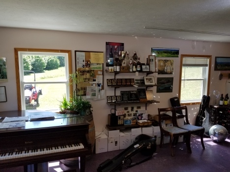 The tasting room with its awards, photos and piano.